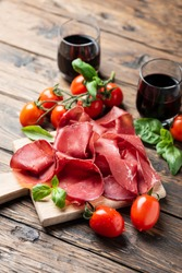 Italian antipasto with bresaola and red wine, selective focus image