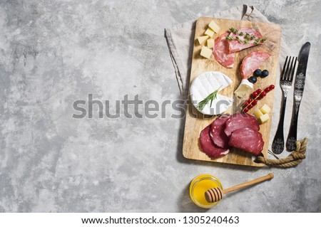 Italian antipasto with prosciutto, salami, Parmesan cheese, brie and Gorgonzola, honey, top view, gray background, space for text