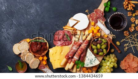 Italian appetizers or antipasto set with gourmet food on black table top view. Mixed delicatessen of cheese and meat snacks with red wine.