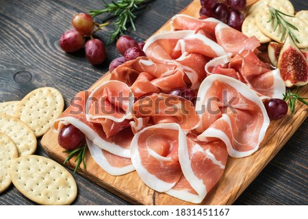 Italian bacon prosciutto crudo or spanish jamon with grapes and crackers on a wooden plate. Food for an aperitif and dinner lunch in the restaurant. food delivery home  Foto stock ©