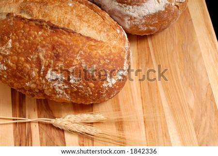 Italian bread loaves with wheat on cutting board
