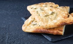 Italian bread - traditional two pieces of focaccia. Focaccia consists of flour, olive oil, water, Fleur de sel, sugar and yeast, topped with rosemary and baked in the oven