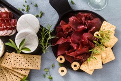 Italian bresaola served sliced on a tray on a table with white wine, crackers, grissini and taralli with aromatic herbs on a blue linen festive tablecloth.