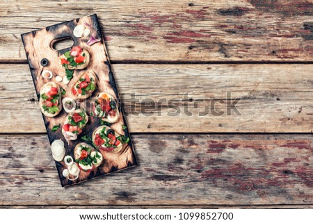Italian bruschetta with cheese and tomatoes on a wooden board. vegetarian Brushetta set. top view. copy space