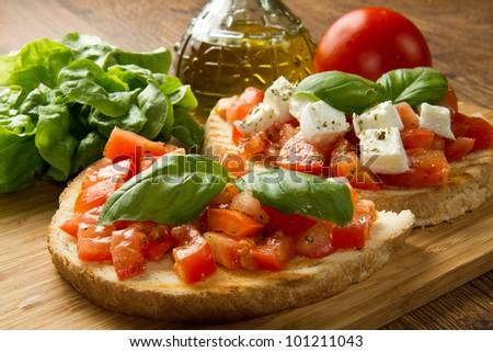 italian bruschetta with fresh tomatoes, basil, garlic, olive oil and cheese