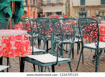 Italian café scene. Chairs and tables outside a stylish outdoor cafe on Piazza Garibaldi in Menaggio, Italy. Cafes, restaurants, gelaterias and shops line this popular spot on the town square.  #1226705125