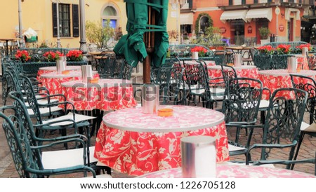 Italian café scene. Chairs and tables outside a stylish outdoor cafe on Piazza Garibaldi in Menaggio, Italy. Cafes, restaurants, gelaterias and shops line this popular spot on the town square.  #1226705128