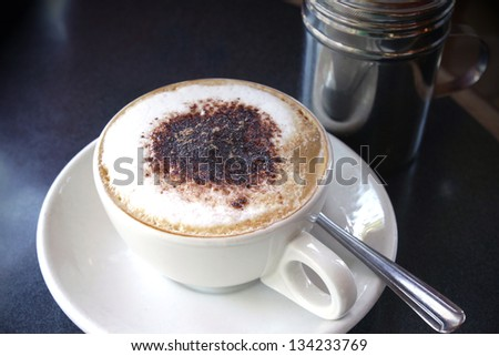 Italian cappuccino on a table with chocolate and cinnamon
