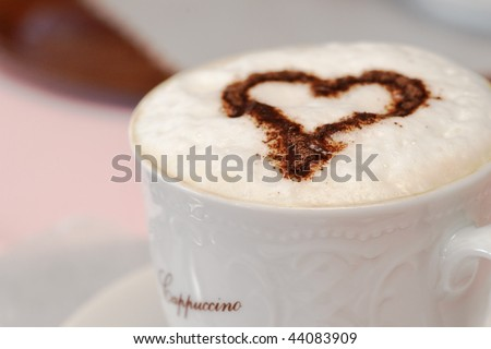 Italian cappuccino with choccolate heart. Shallow depth of field. Valentine's Day concept.