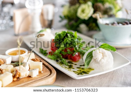 Italian Caprese salad and Cheese plate.. burrata cheese, tomatoes and basil herb leaves. Balsamic vinegar arranged on white plate #1153706323