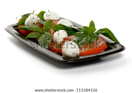 Italian Caprese Salad with Basil, Fresh Mozzarella, Tomatoes and Olive Oil on Black plate isolated on white background
