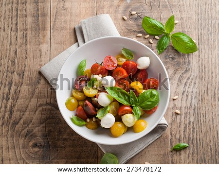 Italian Caprese salad with cherry tomatoes and mini mozzarella, selective focus