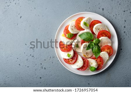 Italian caprese salad with sliced tomatoes, mozzarella, basil, olive oil on a blue background. Top view, place for text. Stok fotoğraf ©