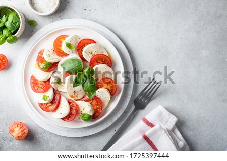 Italian caprese salad with sliced tomatoes, mozzarella, basil, olive oil on a light background. Top view, place for text. Stok fotoğraf ©