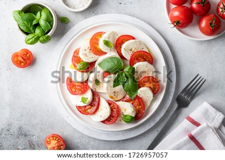 Italian caprese salad with sliced tomatoes, mozzarella, basil, olive oil on a light background. Top view. Stok fotoğraf ©
