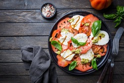 Italian caprese salad with sliced tomatoes, mozzarella cheese, basil, olive oil. Served on black plate over dark wood background. Top view. Rustic style.