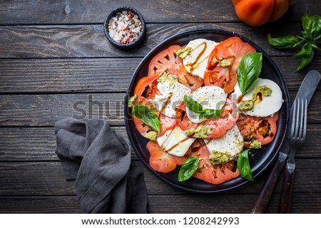 Italian caprese salad with sliced tomatoes, mozzarella cheese, basil, olive oil. Served on black plate over dark wood background. Top view. Rustic style. Stok fotoğraf ©