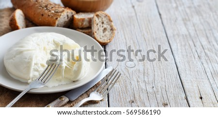 Italian cheese burrata with bread on a wooden background #569586190