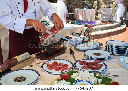Italian Chef cutting Parma raw ham at wedding buffet