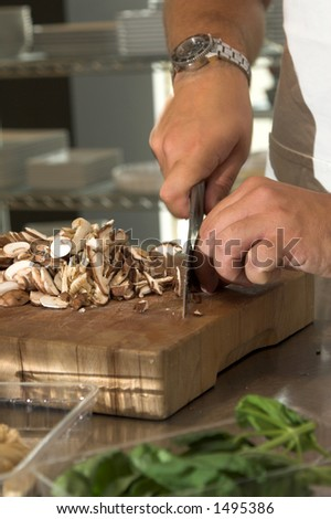 Italian chef working in the kitchen chopping up the champignons
