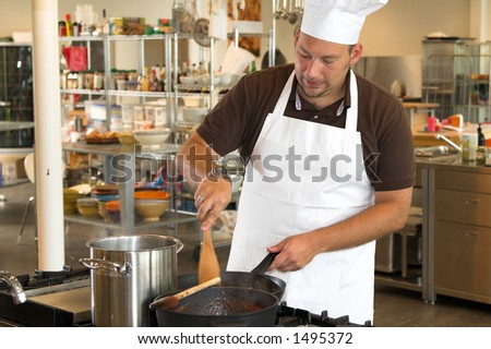 Italian chef working in the kitchen stirring the mushrooms
