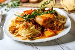 Italian chicken Cacciatore hunter's stew with spaghetti noodles and crusty bread