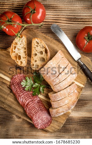 Italian ciabatta bread cut in slices on wooden chopping board with salami. Stock photo ©