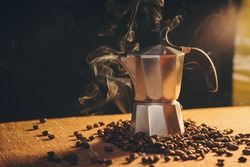 Italian coffee maker and coffee beans on canvas background