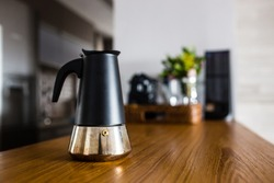 italian coffee maker on wooden kitchen counter with interesting perspective, with cup in focus and blurred background