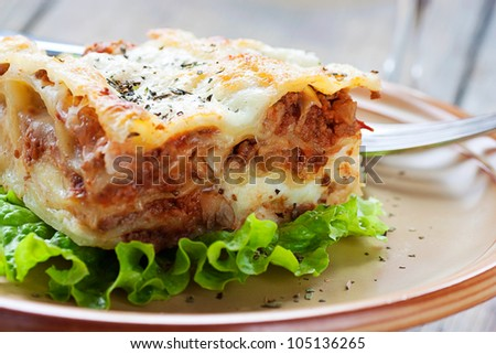 Italian cuisine. Freshly baked homemade lasagna with minced meat and cheese served on a piece of lettuce and red wine.