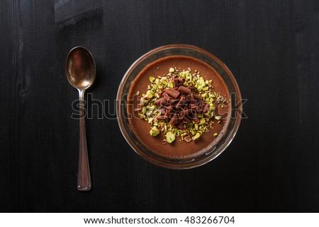 Italian dessert. Chocolate panna cotta with pistachios. Dark wood background #483266704