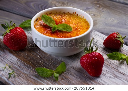 Italian dessert. Delicious cream brulee with strawberries and mint.