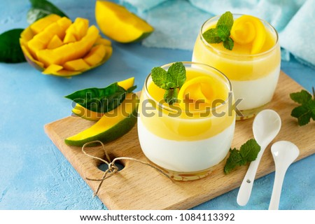 Italian dessert panna cotta decorated with fresh mango and mint on a blue a stone or slate background.