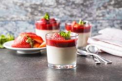 Italian dessert panna cotta in glass with strawberries.