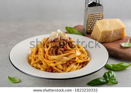 Italian dinner. Egg pasta tagliatelle with bolognese sauce made from meat and tomato sauce, parmesan cheese. Close up.