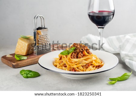 Italian dinner with red wine. Egg pasta tagliatelle with bolognese sauce made from meat and tomato sauce, parmesan cheese. Light grey background.