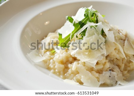 Italian dish risotto with wild white mushrooms and Parmesan cheese in a white plate