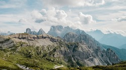 Italian Dolomites, Tre Cime - Rifugio Lavaredo - stony road around Tre Cime .Peak in the clouds. Aerial shot. Beautiful sky and clouds behinds the moutains and valley.