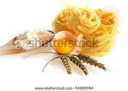 Italian egg pasta fettuccine nest on white background - stock photo