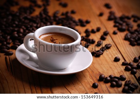 Italian espresso in white cup with coffee beans