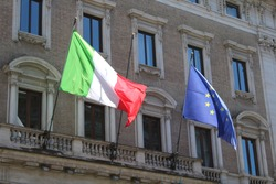Italian flag and european union flag on the front if a building in rome italy