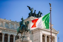 Italian flag on background on famous Vittoriano with gigantic equestrian statue of King Vittorio Emanuele II in Rome