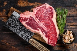 Italian Florentine T-bone beef meat Steak with herbs on a wooden cutting board. Dark wooden background. Top view