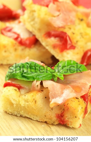Italian focaccia bread with ham and tomatoes, topped with a leaf of fresh basil