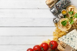 Italian food background on rustic wood boards with copyspace, with tagliatelli pasta, tomatoes, basil, cheese, grossini and condiments