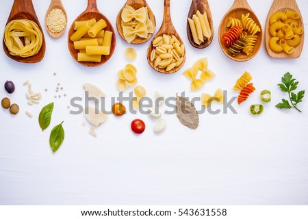 Italian food concept .Various kind of pasta with ingredients sweet basil ,tomato ,garlic ,parsley ,bay leaves ,pepper ,pine nut  and parmesan cheese on white wooden background flat lay and copy space. Foto stock ©