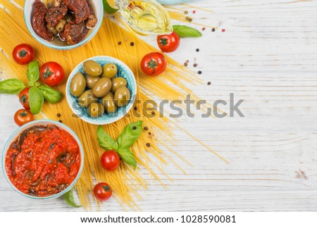 Italian food cooking concept. Ingredients for preparation pasta spaghetti - tomato, olive oil, spices, herbs, green olives, tomato sauce, white wooden background. Flat lay with copy space for text #1028590081