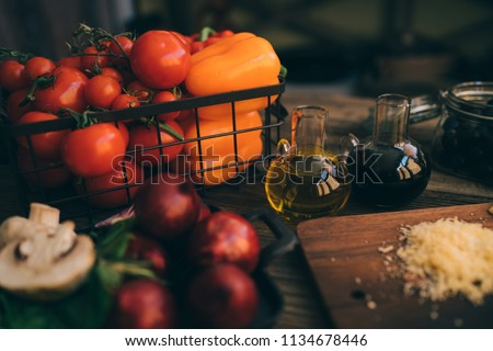 Italian food cooking ingredients on dark rustic background. Healthy vegetarian eating and cooking with various vegetables ingredients. Clean food concept. Toned image. Healthy foods.