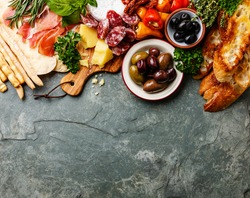 Italian food ingredients background with ham, salami, parmesan, olives, bread sticks