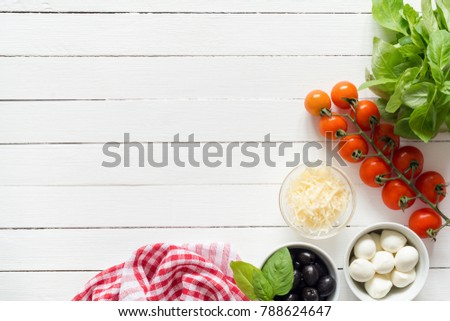 Italian food ingredients for cooking on white table. Parmesan cheese, cherry tomatoes, olives, mozzarella cheese and basil. Pizza ingredients